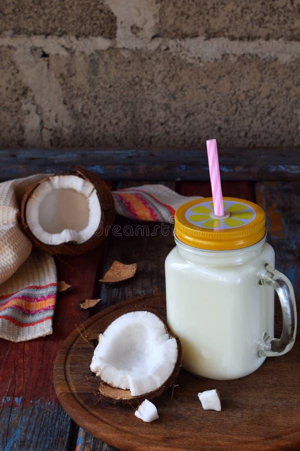 Leche de coco en botella con los Cocos quebrados en fondo de madera Cóctel delicioso de la leche Copie el espacio fotos de archivo libres de regalías