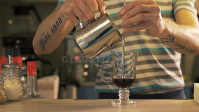 Leche de colada de Barista en la taza de cristal del café en cierre de la cafetería para arriba imagen de archivo
