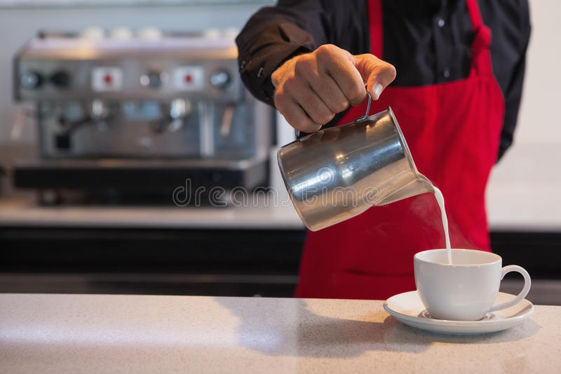 Leche de colada de Barista en la taza de café fotos de archivo libres de regalías
