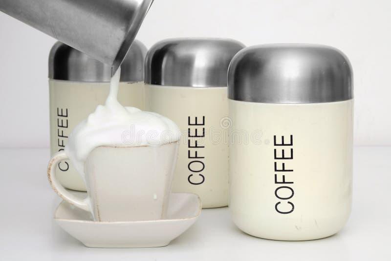 Leche de colada en la taza de coffe. imagen de archivo