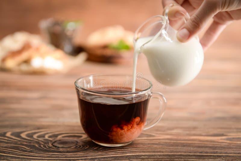 Leche de colada de la mujer en la taza de cristal con té aromático en la tabla foto de archivo