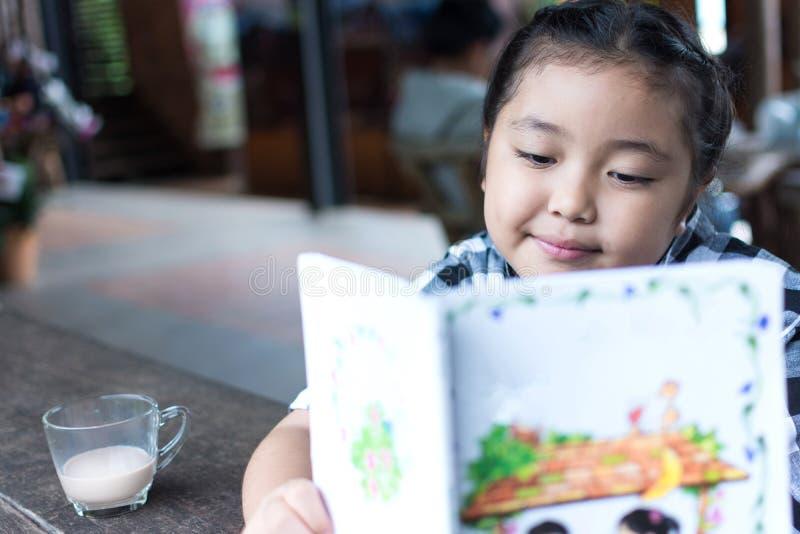 Leche de consumo de la muchacha linda asiática y libro leído en cafetería foto de archivo