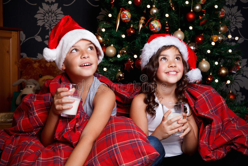 Leche de consumo de los niños dulces en la cama fotos de archivo libres de regalías