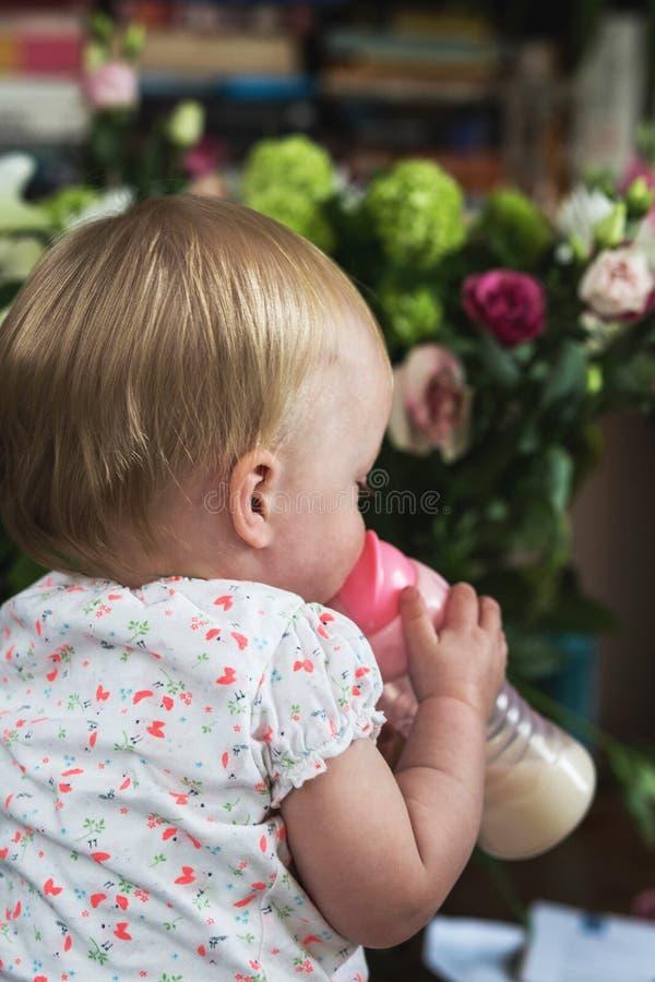 Leche de consumo del ni?o del beb? de la botella, adorable y lindo fotografía de archivo