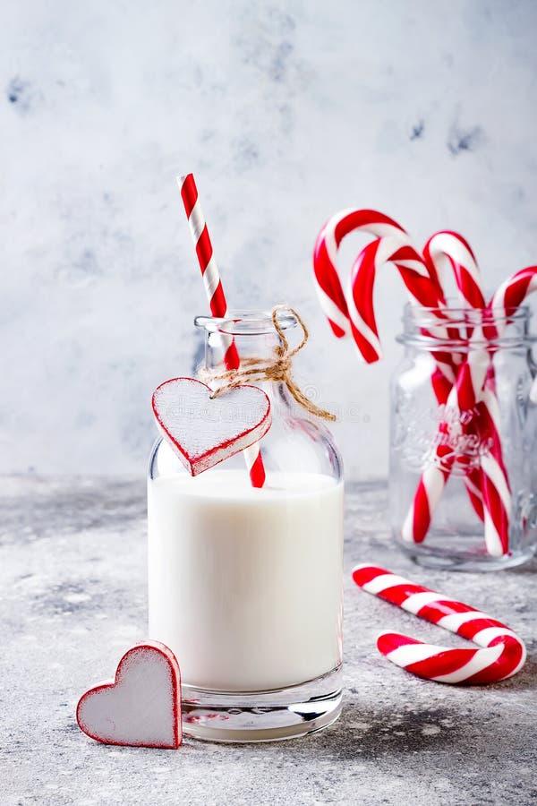 Leche de la Navidad para Papá Noel en botella con el bastón de caramelo de la paja y de hierbabuena Bebida de la celebración de d imagen de archivo libre de regalías