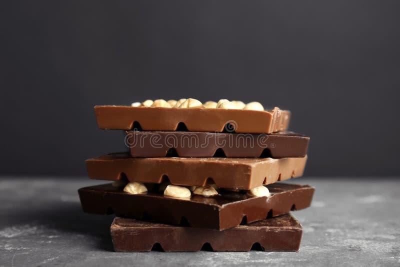 Leche deliciosa y barras de chocolate oscuras con la nuez en la tabla fotos de archivo
