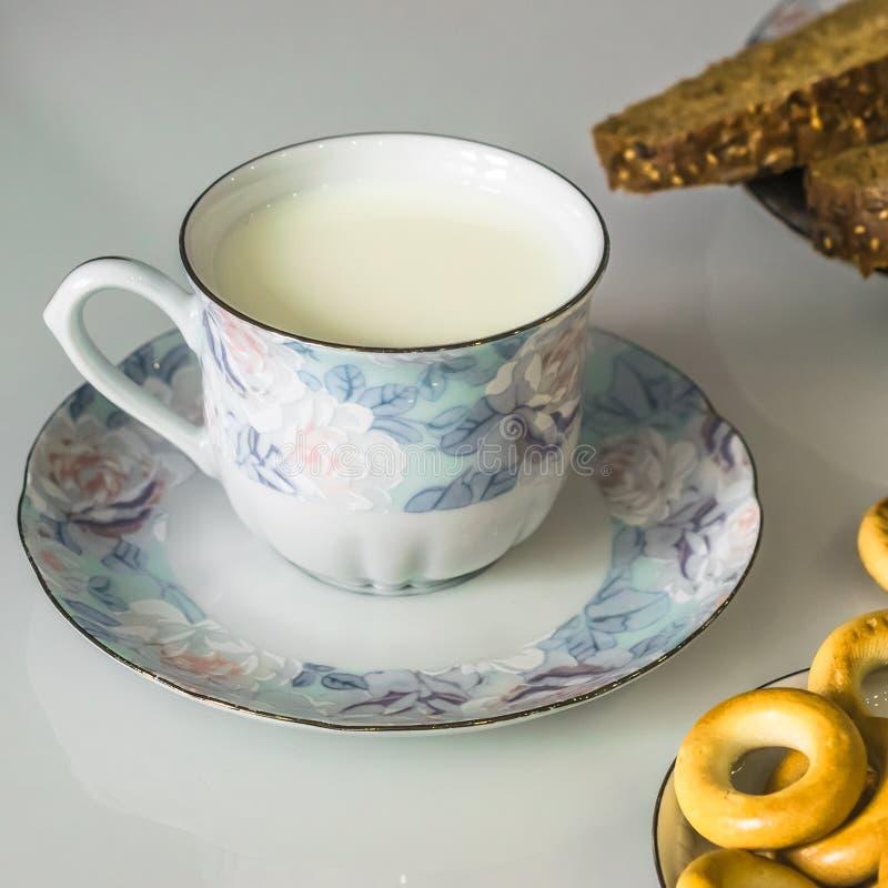 Leche en una taza en la tabla con el pan, secándose imagen de archivo