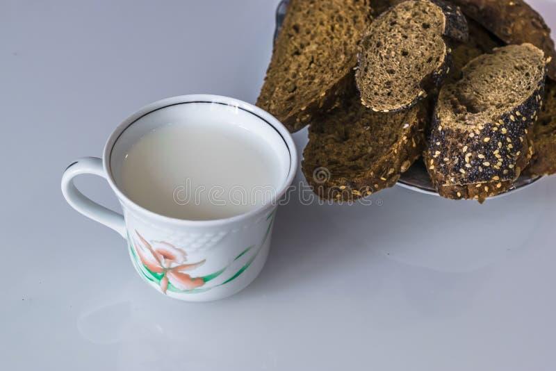 Leche en una taza en la tabla con el pan, secándose imagenes de archivo