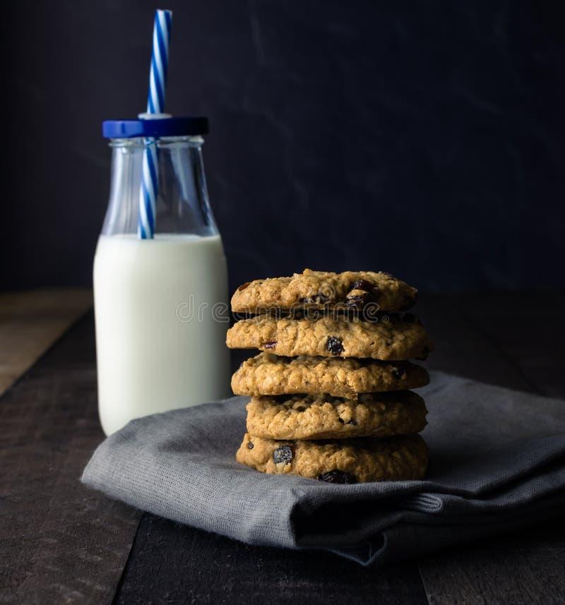 Leche fría en botella con las galletas de pasa deliciosas húmedas de la harina de avena fotos de archivo libres de regalías