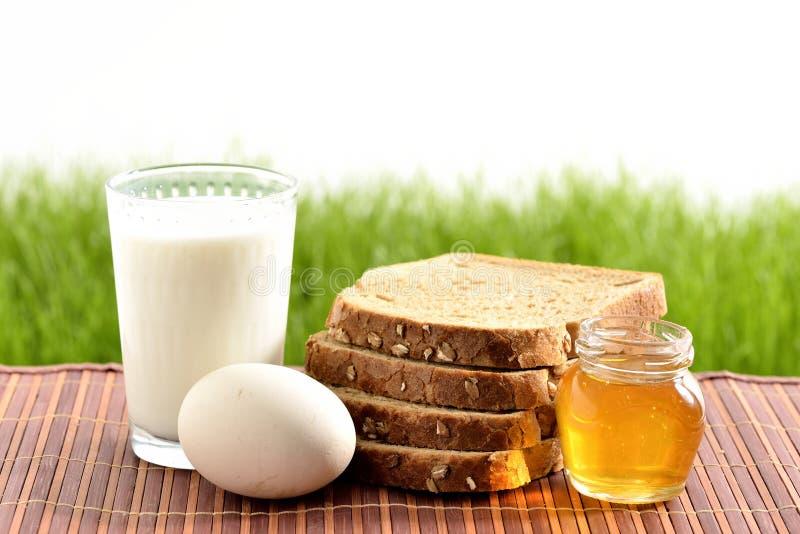 Leche, miel y huevo con pan fotos de archivo libres de regalías
