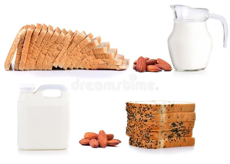 Leche y almendras frescas y rebanada del pan aislada en blanco fotos de archivo