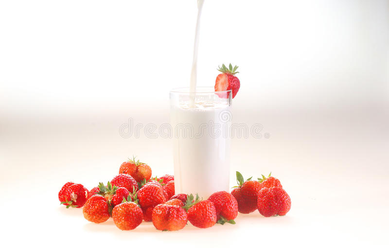 Leche y fresa en un fondo blanco, flujos lácteos en un transporte fotografía de archivo libre de regalías