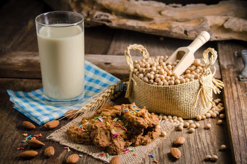 Leche y galletas de soja en una tabla de madera fotografía de archivo