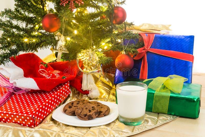 Leche y galletas para Papá Noel debajo del árbol de navidad fotografía de archivo libre de regalías