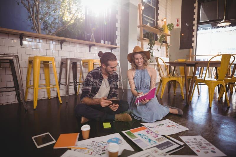 Lechería que muestra profesional femenina joven al colega masculino en la cafetería foto de archivo libre de regalías