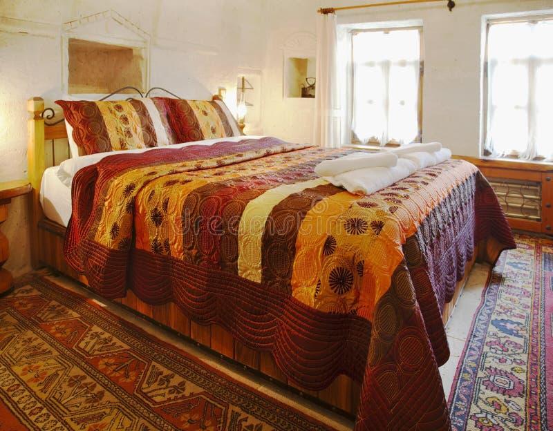 Lecho coloreado multi del dormitorio de la cueva del diseño interior imágenes de archivo libres de regalías