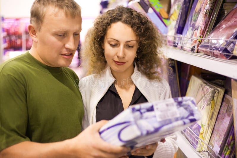 Lecho de compra del hombre joven y de la mujer en supermercado imagen de archivo libre de regalías