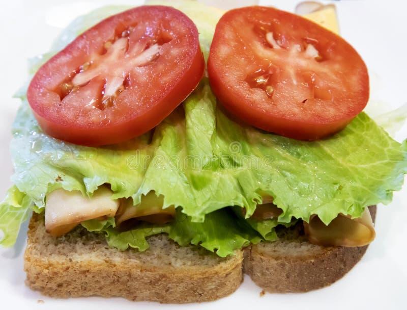 Lechuga, tomate, bocadillo de pollo en el trigo integral foto de archivo