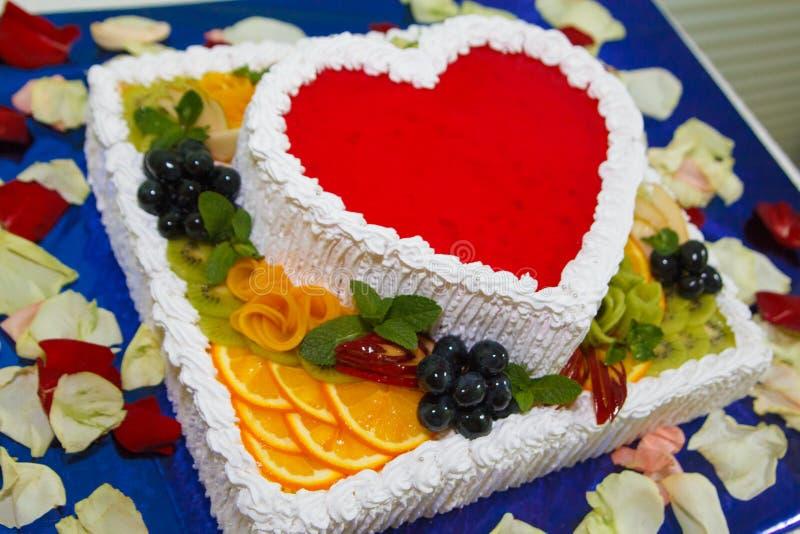 Leckerer sahniger Kuchen in Form eines roten Geleeherzens mit Früchten und buntem Abschluss der Beeren oben stockfotografie