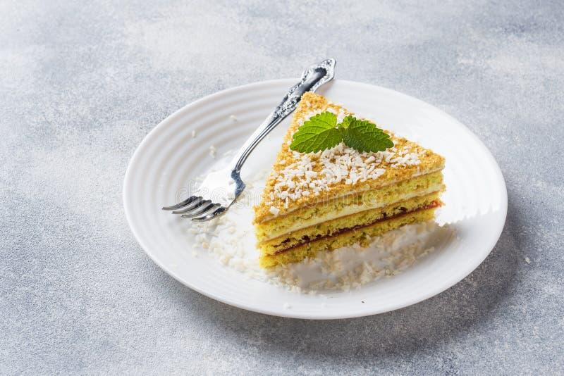 Leckeres Stück Puffkuchen mit Buttercreme und Beerenmarmelade auf einem Teller mit Minze Graubetonhintergrund Leerzeichen kopiere stockfoto