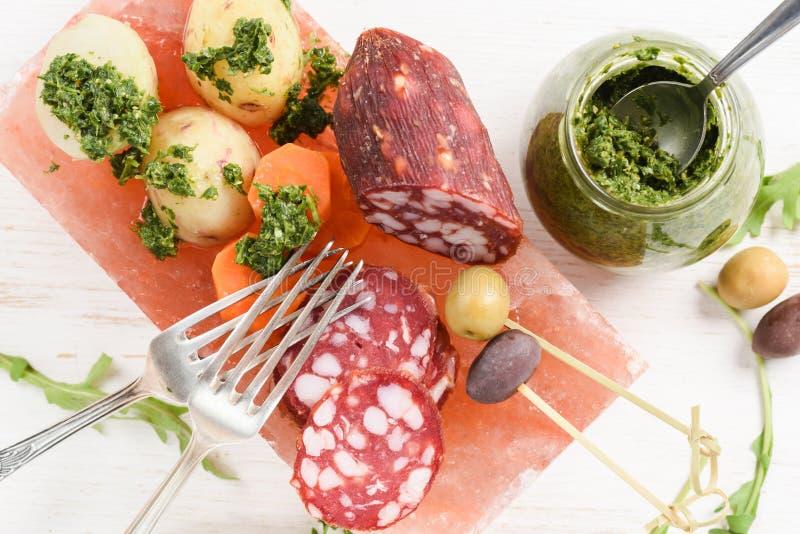 Lecksteinkochen Geräucherte Salami, Kartoffeln, Karotten, Arugula, g stockfotos