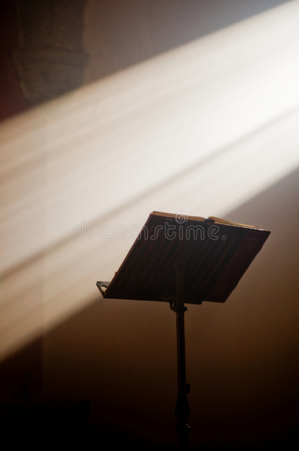 Lectern in altar with a holy bible. Lectern in a church with a holy bible and a ray of divine light stock images