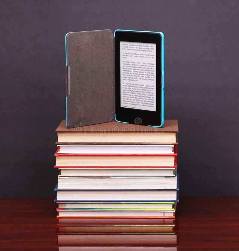 Lecteur électronique de livre et livres de pile vieux sur le bureau en bois image stock