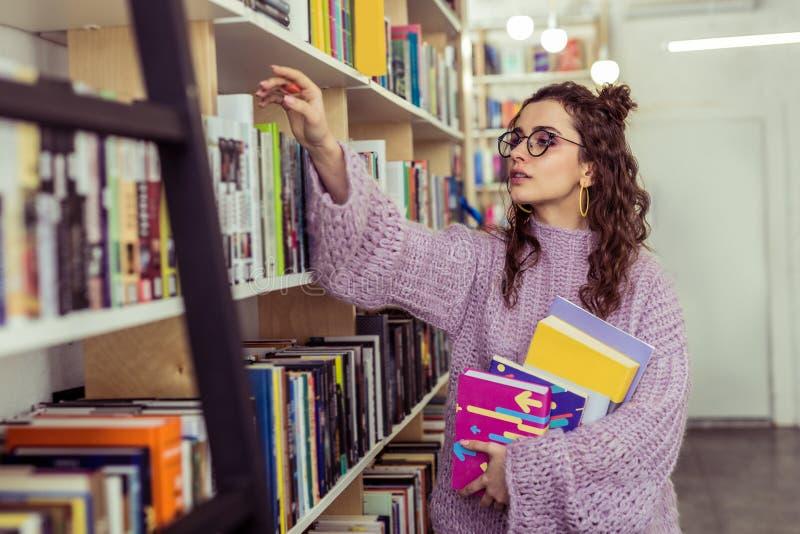 Lecteur agréable intéressé rassemblant activement de nouveaux livres photo libre de droits