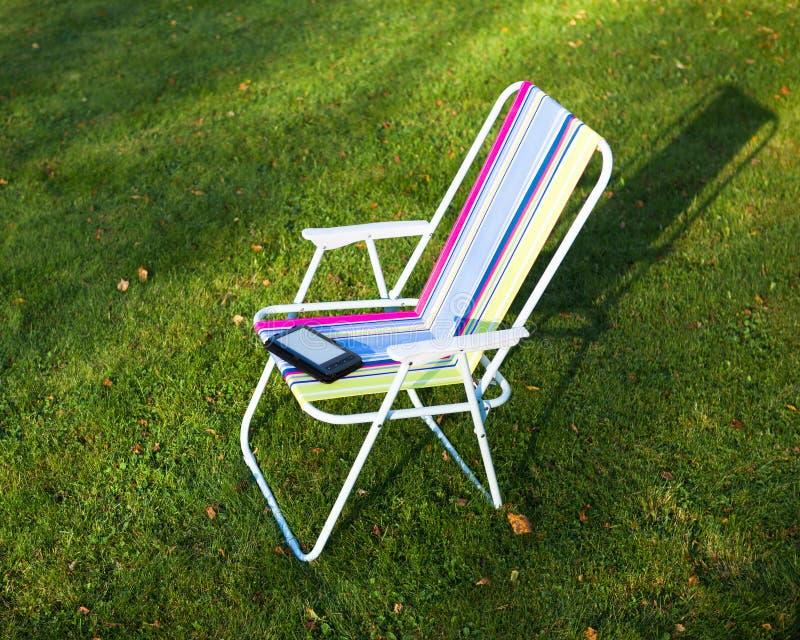 Lecteur d'EBook sur la chaise, fond d'herbe images libres de droits
