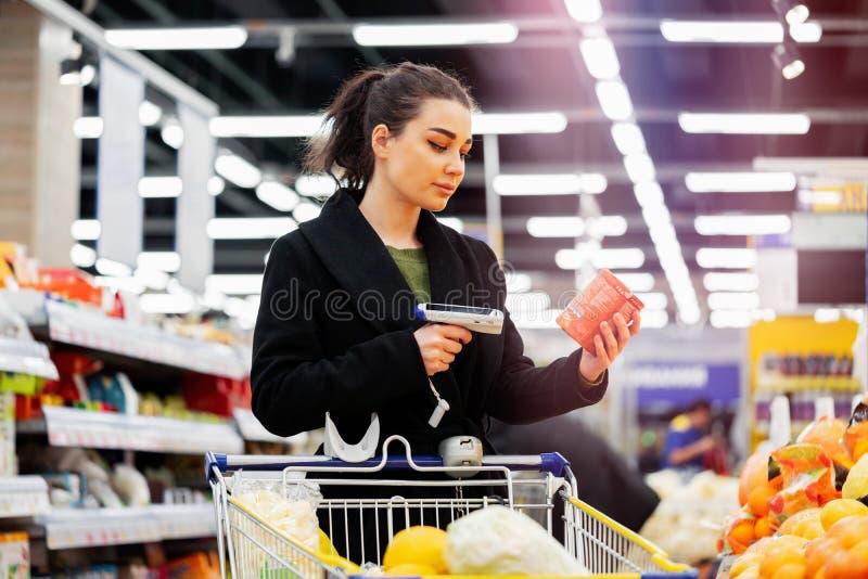 Lecteur de code à barres de participation de femme et produits de balayage dans le magasin photographie stock libre de droits