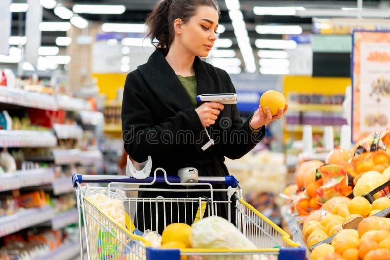 Lecteur de code ? barres de participation de femme et produits de balayage dans le magasin photo libre de droits