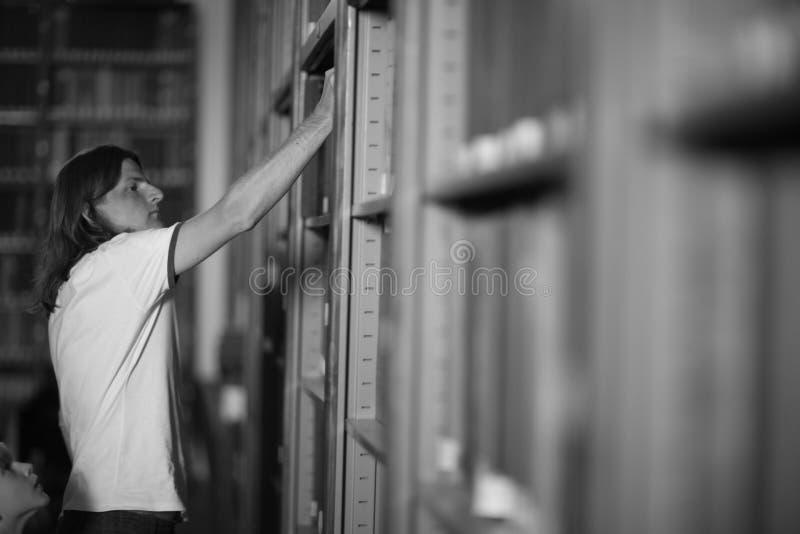 Lecteur prenant un livre dans la bibliothèque photo libre de droits