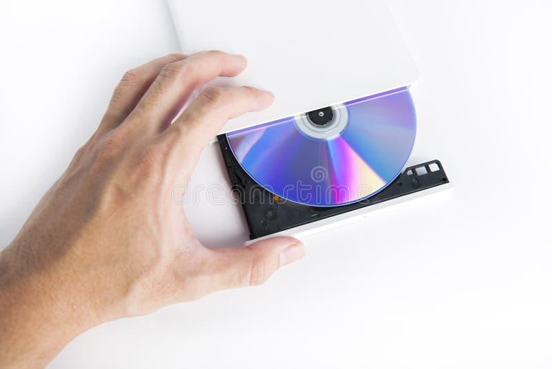 Lector cd externo de la hornilla del DVD con la mano foto de archivo libre de regalías