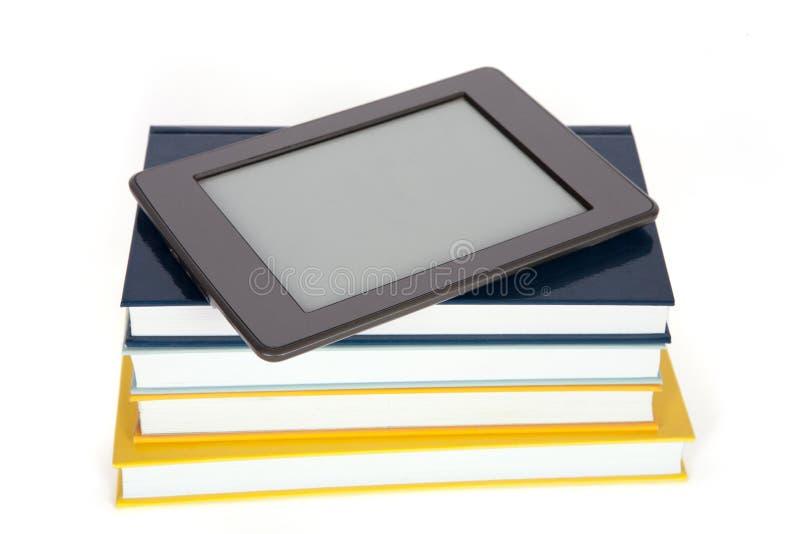 Lector de Ebook con la pantalla vacía encima de la pila de libros de papel fotografía de archivo libre de regalías