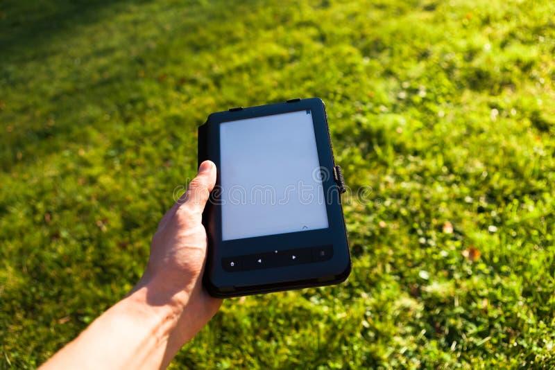 Lector de EBook a disposición, fondo de la hierba verde imágenes de archivo libres de regalías