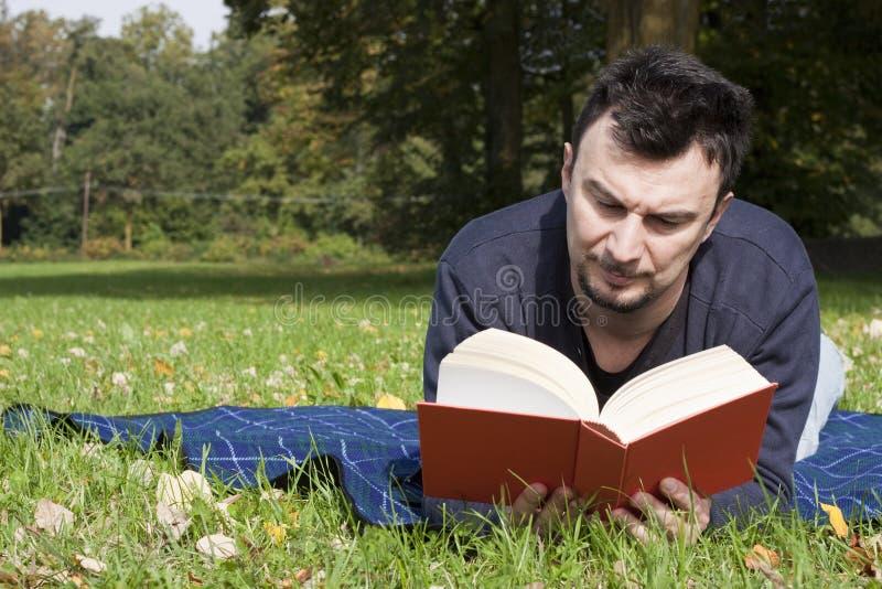Lectura adulta joven en el parque fotografía de archivo