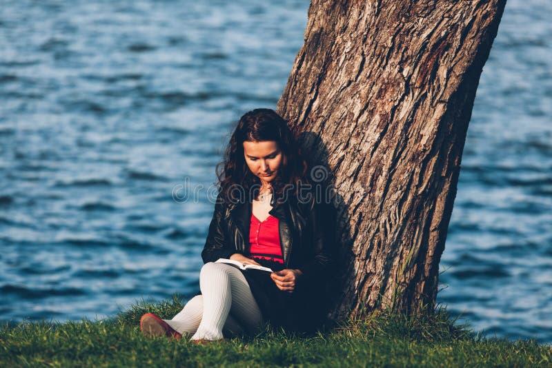 Lectura cerca de un lago fotos de archivo libres de regalías