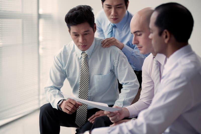 Lectura de informe financiero foto de archivo libre de regalías