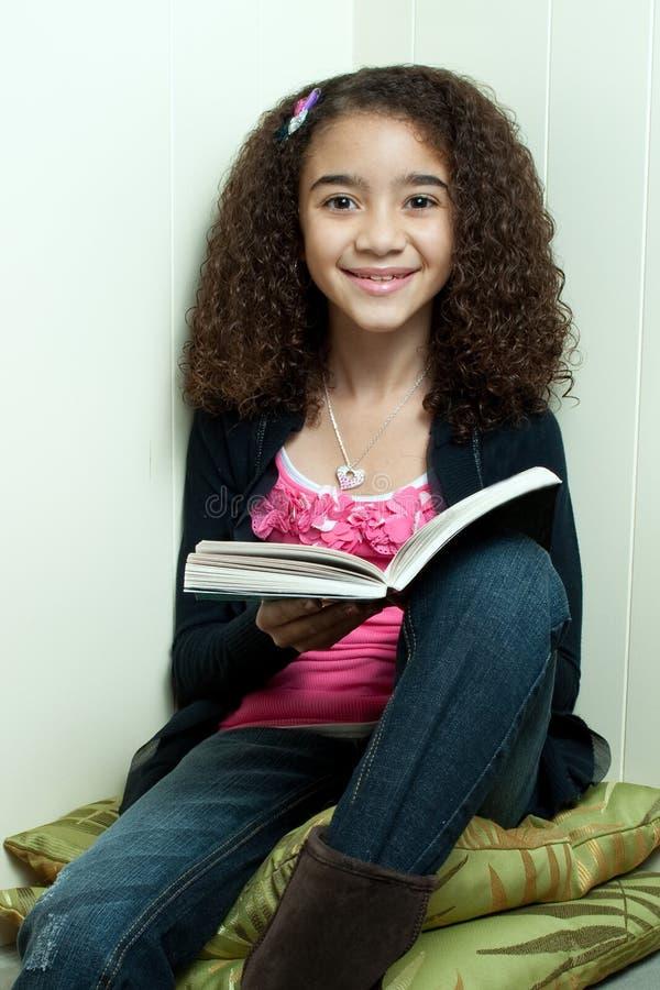 Lectura de la chica joven en esquina imagen de archivo