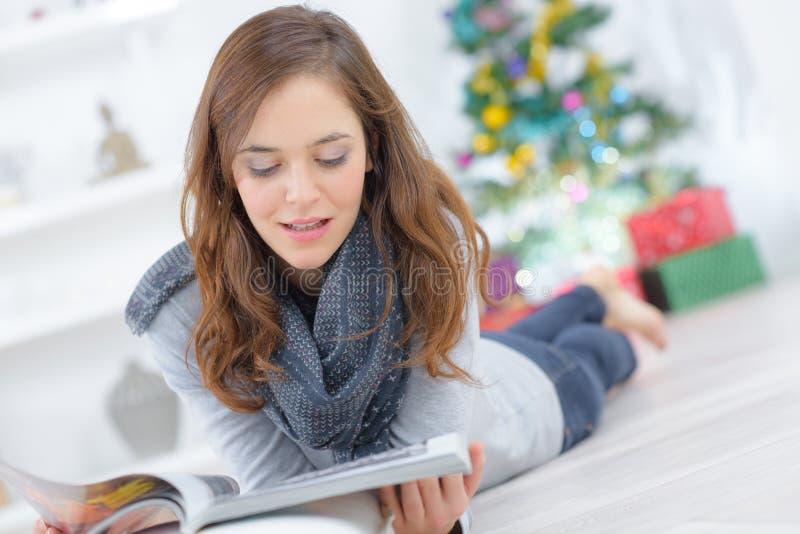 Lectura de la chica joven mientras que pone en piso foto de archivo