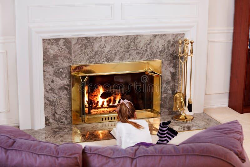 Lectura de la chica joven por el fuego imagen de archivo libre de regalías