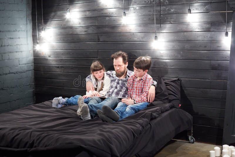Lectura de la familia de la tarde el padre lee a ni?os un libro antes de irse a la cama imágenes de archivo libres de regalías