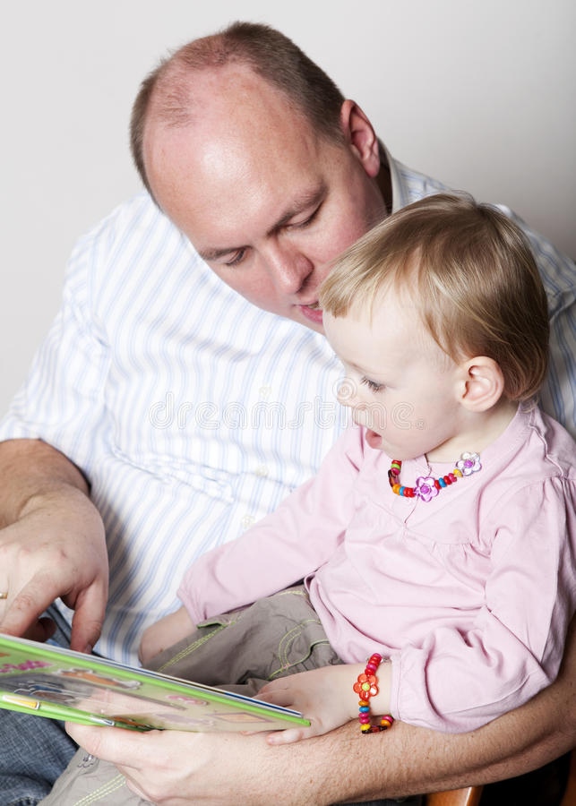 Lectura de la hija del padre y del bebé fotografía de archivo libre de regalías