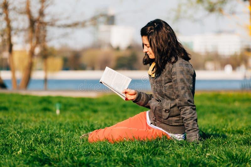 Lectura de la muchacha en el parque fotos de archivo libres de regalías