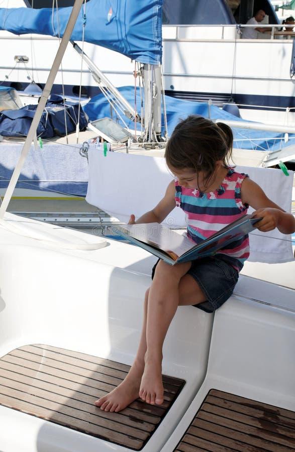 Lectura de la muchacha en el yate imagenes de archivo