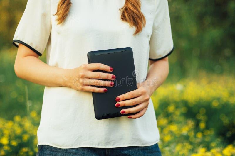 Lectura de la muchacha en la tableta digital en la hierba Mujer joven que usa su tableta digital al aire libre Trabajo joven en s foto de archivo libre de regalías