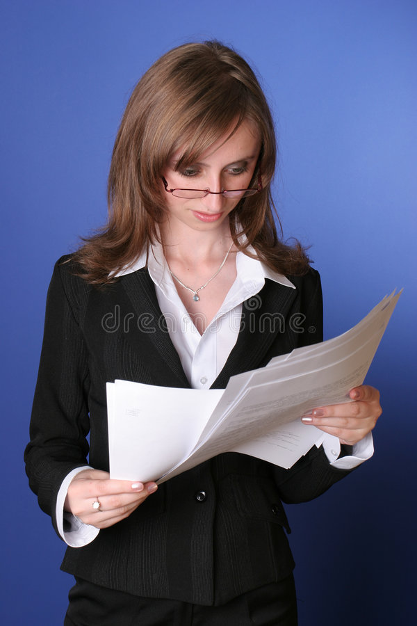 Lectura de la mujer de negocios cuidadosamente un fichero fotografía de archivo
