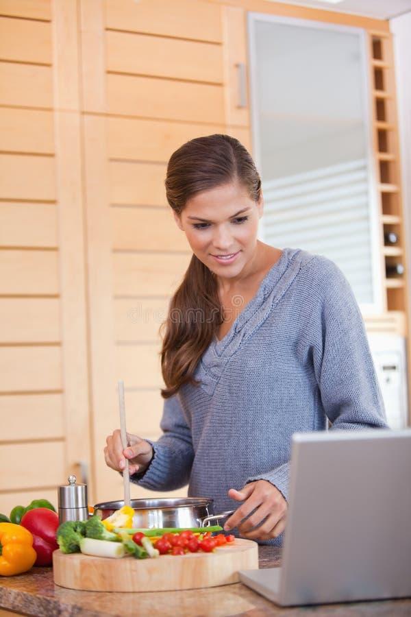 Lectura de la mujer de una receta mientras que cocina fotos de archivo libres de regalías