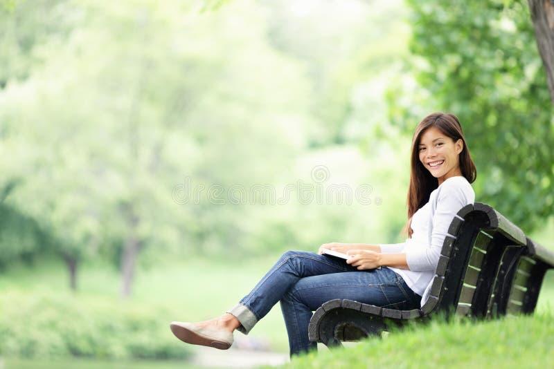Lectura de la mujer del parque en banco fotos de archivo