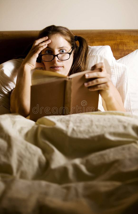 Lectura de la mujer en cama foto de archivo libre de regalías